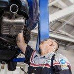 auto-mechanic-working-under-car